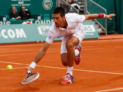 Novak Djokovic of Serbia dips low to hit this backhand during his victory Wednesday against Andreas Seppi of Italy.