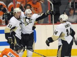 Penguins center Jordan Staal, left, celebrates his goal with teammates right wing James Neal (18) and left wing Chris Kunitz (14) during the second period of Game 3, Staal had a hat trick as Pittsburgh stayed alive in the series.
