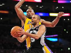San Antonio guard Tony Parker (9) goes in for a basket against the defense of Los Angeles forward Metta World Peace (15) during the first half of the Spurs' win over the Lakers on Tuesday night at Los Angeles.