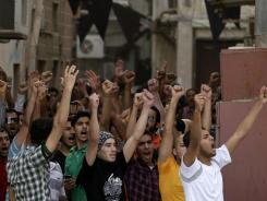 Bahraini anti-government protesters chant slogans toward riot police in Manama Thursday. Security forces fanned out across Bahrain's capital in attempts to quell widening unrest that threatened to overshadow the return of the Formula One Grand Prix.