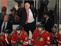 Blackhawks coach Joel Quenneville tries to get referees to stop play after an injury to Marian Hossa.