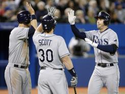 Evan Longoria, right, is congratulated by Ben Zobrist, left, and Luke Scott after belting a three-run homer Thursday.