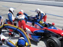 Mike Conway of AJ Foyt Racing pulls in for a pit stop as members of the ABC Supply crew work on his car.