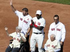 Former Boston Red Sox catcher Jason Varitek, top left, stands with, current designated hitter David Ortiz, top center, former pitcher Tim Wakefield, top right, and former players Bobby Doerr, seated right, and Johnny Pesky, seated left, on the field during ceremonies.