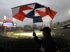 A fan leaves Comerica Park after the Detroit Tigers-Texas Rangers baseball game was postponed due to rain in Detroit on Friday.