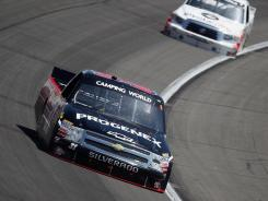 James Buescher, driver of the #31 Progenex Chevrolet, leads Todd Bodine, driver of the #11 Toyota Care Toyota, during the NASCAR Camping World Series SFP 250 at Kansas Speedway. Buescher won the race, his first Truck Series victory of the season.