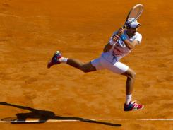 Novak Djokovic of Serbia runs down a backhand during his victory against Tomas Berdych of the Czech Republic.