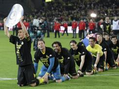 Dortmund's Sebastian Kehl holds a mock tropy as he celebrates with his teammates Saturday after they won their second consecutive German Bundesliga title.