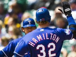 Josh Hamilton goes high-five with Ian Kinsler after homering to start an eight-run first for the Rangers at Comerica Park.