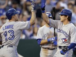 Toronto Blue Jays' Colby Rasmus, right, celebrates with teammate Brett Lawrie (13) after hitting a two-run home run during the sixth inning of their game against the Kansas City Royals. Rasmus homered twice and pitcher Jays Drew Hutchinson picked up a win in his MLB debut.