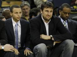 Injured Warriors Stephen Curry, left, and Andrew Bogut grab some pine during a game this month.
