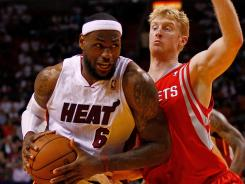 Miami's LeBron James drives on Houston's Chase Budinger during the Heat's win over the Rockets on Sunday.