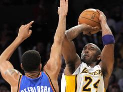 Los Angeles guard Kobe Bryant, right, puts up a shot as Oklahoma City guard Thabo Sefolosha defends during overtime of the Lakers' 114-106 win over the Thunder on Sunday.