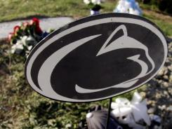 A Nittany Lion marker decorated the gravesite of former football coach Joe Paterno last week. Candelight vigils have been conducted there, and teh cemetery last week decided to start closing a dusk.