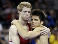 Nick Simmons, left, hugs Henry Cejudo after their 121-pound freestyle match at the U.S. Olympic Wrestling Team Trials in Iowa City on Sunday. Simmons defeated Cejudo, who retired from the sport following the match.