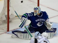 Jarret Stoll, bottom, scores the game-winning goal against Canucks goalie Cory Schneider during overtime of Game 5 to clinch the series for the Kings.