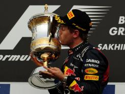 German driver Sebastian Vettel kisses the trophy after winning the Bahrain Formula One Grand Prix on Sunday.