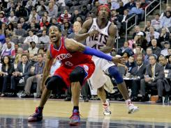 Sixers forward Andre Iguodala and Nets forward Gerald Wallace battle for a rebound during the Nets final game at the Prudential Center in Newark, N.J.