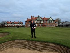 Peter Dawson, the Chief Executive of the R&A, holds the Claret Jug on the 18th green in front of the clubhouse at Royal Lytham and St Annes Golf Club.