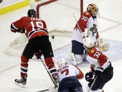 The Devils' Travis Zajac (19) scores the game-winning goal on Panthers goalie Scott Clemmensen at 5:39 of overtime to force a Game 7 back in Florida.