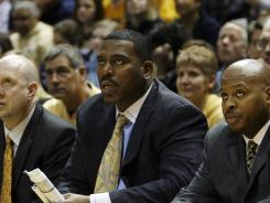 Tony Benford (second from right) looks on during a Marquette game.