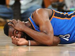 Oklahoma City's James Harden holds his head after taking an elbow from L.A. Laker Metta World Peace during their game Sunday.