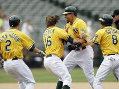 The Athletics' Kila Ka'aihue, second from front right, is mobbed by teammates, from left, Cliff Pennington, Josh Reddick and Kurt Suzuki after driving in the game-winning run in the 14th inning.