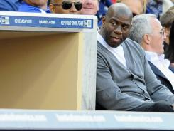 Magic Johnson, new minority of the Dodgers, attends a game against the Padres.