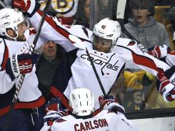 Washington Capitals winger Joel Ward (42) is congratulated by teammates after his series-clinching overtime goal against the Boston Bruins.