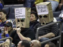 Charlotte Bobcats fans wear bags over their heads as they watch the second half of the Bobcats' final loss to the New York Knicks in Charlotte on Thursday.