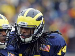 In this Nov. 19, 2011, photo, Michigan linebacker J.B. Fitzgerald (42) holds up the ball he recovered from a Nebraska fumble, next to safety Josh Furman (14), during NCAA college football game in Ann Arbor, Mich. Michigan suspended backup safety Furman two months after his arrest on suspicion of assault.
