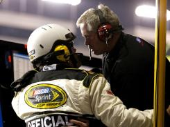 Crew chief Bob Osborne, right, is told by a NASCAR official about the ruling the Carl Edwards jumped a restart with 82 laps to go.