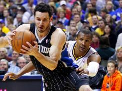 Orlando Magic shooting guard J.J. Redick (7) dribbles past Indiana Pacers shooting guard Leandro Barbosa (28) during the first half of the Magic's Game 1 victory over the Pacers on Saturday at Indianapolis.