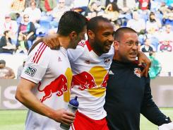 The New York Red Bulls' Thierry Henry is helped off the field in pain after injuring his leg against the New England Revolution on Saturday in Harrison, N.J.