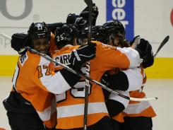 The Flyers celebrate their 4-3 overtime victory Sunday against the Devils in Game 1 of the Eastern Conference semifinals.