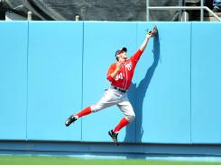 Nationals rookie right fielder Bryce Harper reaches to catch a fly ball in the fourth inning.
