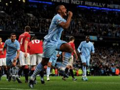 Vincent Kompany of Manchester City celebrates scoring the opening goal during the Barclays Premier League match against Manchester United at the Etihad Stadium on Monday in Manchester, England.