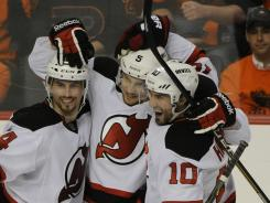 Devils teammates Adam Henrique, left, Adam Larsson and Peter Harrold celebrate Larsson's third-period goal against the Flyers.