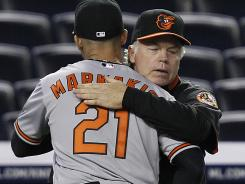 Orioles manager Buck Showalter embraces outfielder Nick Markakis after Baltimore's 7-1 road victory Tuesday against the Yankees.