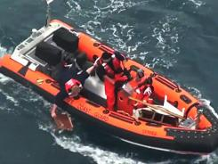 In this image taken from U.S. Coast Guard video, a rescuer retrieves a piece of debris from the ocean off the Baja Calif., near Ensenada, Mexico on Sunday. The 37-foot racing sailboat Aegean, carrying a crew of four, was reported missing Saturday, the U.S. Coast Guard said.