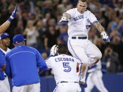 The Blue Jays' Brett Lawrie jumps up to celebrate with teammates after hitting the game-winning home run against the Rangers Monday in Toronto.