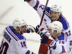 New York Rangers right wing Marian Gaborik (10) celebrates his winning goal against the Washington Capitals with teammates Carl Hagelin (62) and Marc Staal (18).