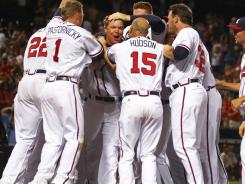 Chipper Jones, middle, celebrates with Braves teammates after hitting a game-winning, two-run homer in the 11th inning against the Phillies on Wednesday night.