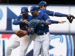 Blue Jays players Eric Thames, left, Jose Bautista, middle, and Colby Rasmus celebrate after beating the Rangers for the second consecutive game on Wednesday.