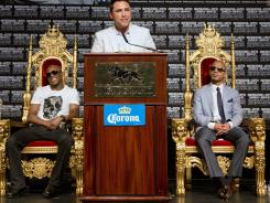 Golden Boy's Oscar de la Hoya talks as Floyd Mayweather Jr., left, and Miguel Cotto listen during their final press conference.