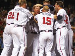 Chipper Jones, center, celebrates with his Braves teammates after hitting a game-winning, two-run home run in the 10th inning to beat the Phillies 15-13.
