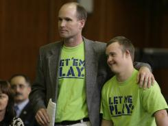 Dean Dompierre, left, and son Eric testified before a Michigan Senate committee hearing Wednesday. Dompierre supports an age-limite waiver that would allow his 19-year-old son with Down Syndrome to play football and basketball next season.