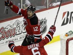 Alexei Ponikarovsky (12) celebrates his game-winning goal in overtime with teammate Andy Greene that lifted the Devils to a 4-3 win over the Flyers in Game 3.
