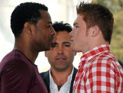 """With promoter Oscar De La Hoya looking on, Saul """"Canelo"""" Alvarez, right, and Shane Mosley pose in Mexico City in March during a press tour for their light middleweight title fight on Saturday."""