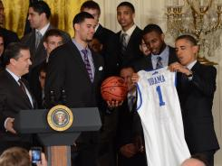 John Calipari, left, and national champion Kentucky present President Obama with a signed basketball and jersey.
